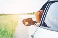 Voyageuse de femme d'Asain avec la voiture sur la belle route photo stock