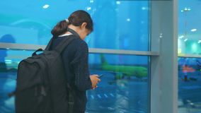 Voyageuse de fille avec un concept d'a?roport de vols d'avion de sac ? dos l'adolescente de fille avec un smartphone regarde la f clips vidéos