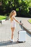 Voyageuse de fille avec une valise blanche Photographie stock