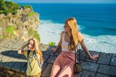 Voyageuses de maman et de fils dans le temple de Pura Luhur Uluwatu, Bali, Indonésie Paysage étonnant - falaise avec le ciel bleu photos libres de droits