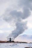 Voyagez en Islande, un homme avec de la fumée du souterrain dans le secteur géothermique Hverir en hiver, Islande Image libre de droits