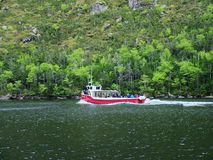 Voyagez le bateau et les touristes sur l'étang occidental de ruisseau à Gros Morne National Park Images libres de droits