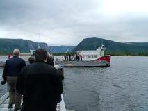 Voyagez le bateau et les touristes sur l'étang occidental de ruisseau à Gros Morne National Park Images stock