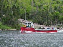 Voyagez le bateau et les touristes sur l'étang occidental de ruisseau à Gros Morne National Park Photos libres de droits