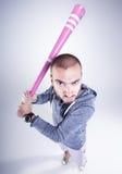 Voyou drôle avec une batte de baseball rose semblant fâchée dans le studio Image libre de droits