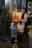 Religion. VOYUTYN, UKRAINE - 14 October 2008: Ukrainian parishioners of the Orthodox Church light up candles during the religious celebration Pokrov Stock Photos