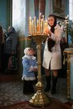 Family. VOYUTYN, UKRAINE - 14 October 2008: Ukrainian parishioners of the Orthodox Church light up candles during the religious celebration Pokrov Royalty Free Stock Images