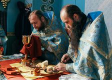 Priests consecrates bread. Voyutyn, Volyn / UKRAINE - October 14 2014: Priests consecrates bread during orthodox liturgy ceremony royalty free stock photo