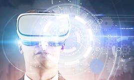 VR玻璃、HUD和嵌齿轮的人在都市风景 免版税库存图片