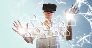VR的妇女与反对蓝色背景的白色房子图表与火光 免版税图库摄影
