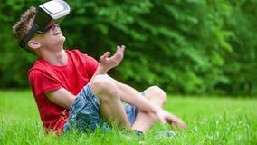 戴VR眼镜的青少年的男孩在公园 股票录像