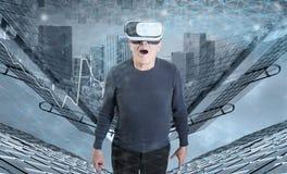 VR耳机的一个老人反对城市大厦背景 库存图片
