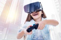 VR耳机的愉快的女孩使用电子游戏控制器 库存图片