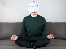VR耳机的男性收养在沙发 库存照片