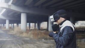 VR 360耳机训练拳打的军事拳击人在户外都市地点的虚拟现实战斗在冬天 库存照片