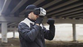 VR 360耳机训练拳打的年轻人拳击手在户外都市地点的虚拟现实战斗在冬天 库存图片