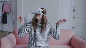 Красивая молодая женская играя игра в стеклах vr Женщина используя шлемофон виртуальной реальности 3D Она сидит на софе и получае видеоматериал