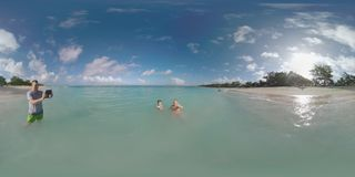 360 VR Family with child bathing in ocean and taking video of vacation on Mauritius Island. 360 VR video. Happy mom and son bathing in clear blue ocean. They stock footage