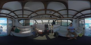 360 VR Family traveling by yacht. Inside view with captain driving vessel. 360 VR video. Inside view of sailing yacht with family and captain. Father taking stock video