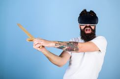 VR gamer concept. Man with beard in VR glasses, light blue background. Guy with head mounted display and sword play. Fighting game in VR. Hipster on shouting stock photo