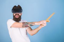 VR gamer concept. Man with beard in VR glasses, light blue background. Guy with head mounted display and sword play. Fighting game in VR. Hipster on shouting royalty free stock photo