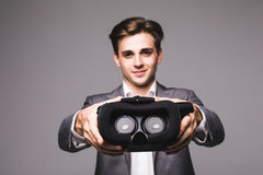VR Goggles. Man give, pointed virtual reality goggles watching movies or playing video games isolated on a white background Royalty Free Stock Images