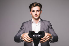 VR Goggles. Man give, pointed virtual reality goggles watching movies or playing video games isolated on a white background Stock Images