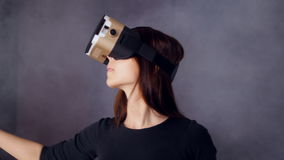 VR gokkenconcept Een meisje die virtuele werkelijkheidshoofdtelefoon dragen die geamuseerd kijken stock video