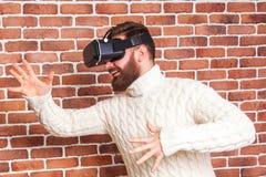 VR-hörlurar med mikrofonteknologi och man hemma nära den bruna väggen Arkivbild