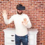 VR-hörlurar med mikrofonteknologi och man hemma nära den bruna väggen Royaltyfria Bilder