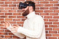 VR-hörlurar med mikrofonteknologi och man hemma nära den bruna väggen Royaltyfri Foto