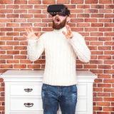 VR-hörlurar med mikrofonteknologi och man hemma nära den bruna väggen Arkivfoto
