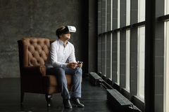 The VR headset design is generic and no logos, Man wearing virtual reality goggles watching movies or playing video games, dark ph Stock Images