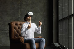 The VR headset design is generic and no logos, Man wearing virtual reality goggles watching movies or playing video games, dark ph. Man wearing virtual reality Royalty Free Stock Photo