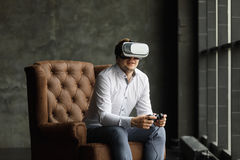 The VR headset design is generic and no logos, Man wearing virtual reality goggles watching movies or playing video games, dark ph. Man wearing virtual reality Stock Images