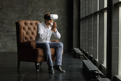 The VR headset design is generic and no logos, Man wearing virtual reality goggles watching movies or playing video games, dark ph Royalty Free Stock Image