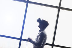 The VR headset design is generic and no logos, Man wearing virtual reality goggles watching movies or playing video games. Standin Royalty Free Stock Photo