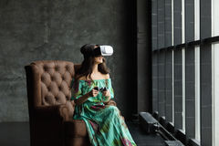 The VR headset design is generic and no logos, Woman with glasses of virtual reality, Sits in a chair, against a dark background. Royalty Free Stock Photography