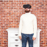 VR headset technology and man at home near brown wall. Royalty Free Stock Images