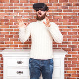 VR headset technology and man at home near brown wall. Stock Photo