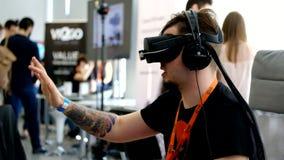 VR-konferensbesökaren testar virtuell verklighethjälmen lager videofilmer