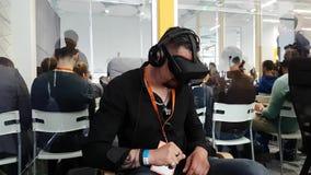 VR-konferensbesökaren testar virtuell verklighethjälmen stock video