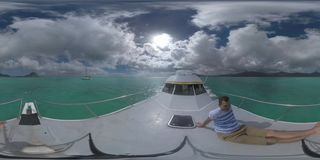 360 VR Man traveling by yacht sailing to Mauritius Island. 360 VR video. Man sitting on the front deck of the yacht sailing towards Mauritius on high speed. View stock video footage