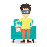 vr man. Young smiling man using vr glasses sits on armchair with popcorn on white background. Home entertainment. Augmented reality, new technologies. 3D film Royalty Free Stock Images
