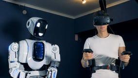 VR-Plattform erhält gepflegt durch einen männlichen Jugendlichen, um einen menschlich ähnlichen Roboter zu manipulieren stock video footage