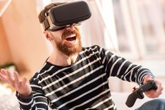 Glad merry man winning in VR game. VR systems. Optimistic bearded happy man carrying controller while laughing and wearing VR headset Stock Photography