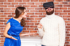 VR technology and conflict between couple. man using vr headset and his wife is angry. VR technology and conflict between couple. men using vr headset and his Royalty Free Stock Images