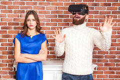 VR technology and conflict between couple. man using vr headset and his wife is angry. VR technology and conflict between couple. men using vr headset and his Stock Photography