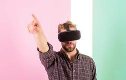 Vr teknologi ger nya tillfällen i teknik Man orakade grabbvirtuell verklighetexponeringsglas, rosa bakgrund hipster royaltyfria foton