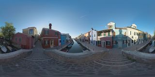 360 VR Townscape of Burano. Rustic scene with colored houses and boats in canal. 360 photo - Looking at Burano from the footbridge. Traditional painted houses royalty free stock image